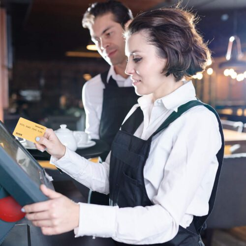 Content attractive young waitress with short hair swiping card through POS terminal while adding information